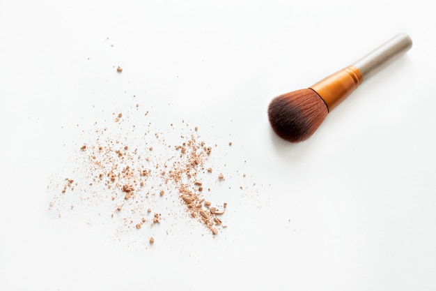 Poudre et pinceaux de maquillage isolés on white
