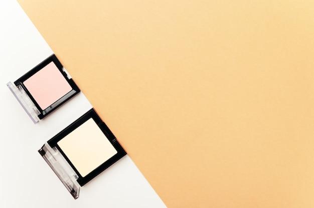 Poudre pour le visage et blush rose dans des étuis carrés ouverts sur beige blanc