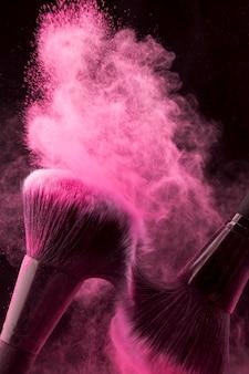 Poudre rose tartinée avec des pinceaux se frottant