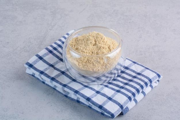 Poudre de sésame mélangée dans une tasse en verre sur une serviette à carreaux.