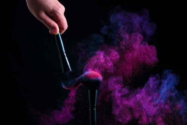 Poudre souffle des pinceaux de maquillage. explosion de poudre sur fond noir