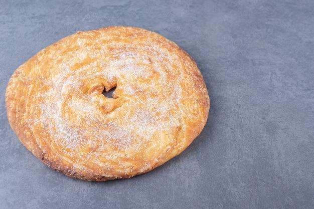 Poudre de sucre sur du pain sur une table en marbre.