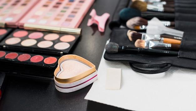 Poudre de surligneur et pinceaux de maquillage sur la table