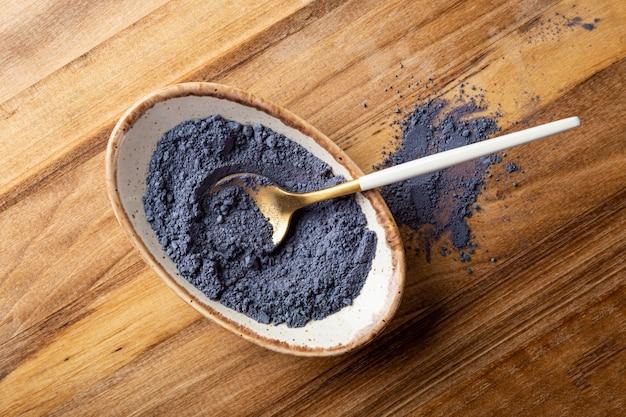Poudre de thé bleu matcha dans un bol nouvelle tendance superaliments aliments sains vue de dessus en gros plan