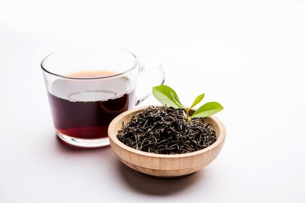 Poudre de thé noir ou poudre sèche avec ou sans feuille verte et chai chaud servi dans une tasse