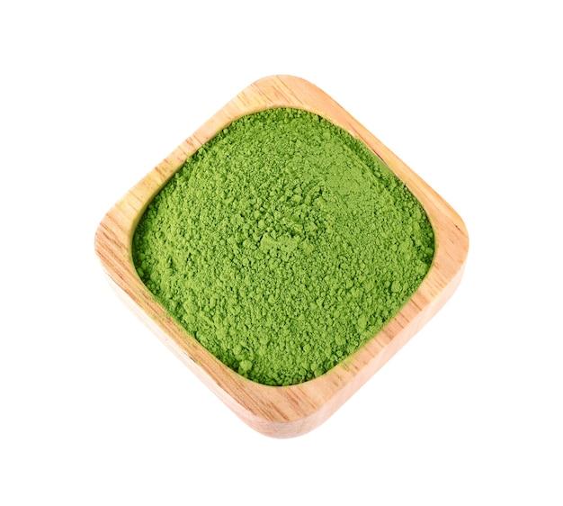 Poudre de thé vert dans un bol en bois sur fond blanc