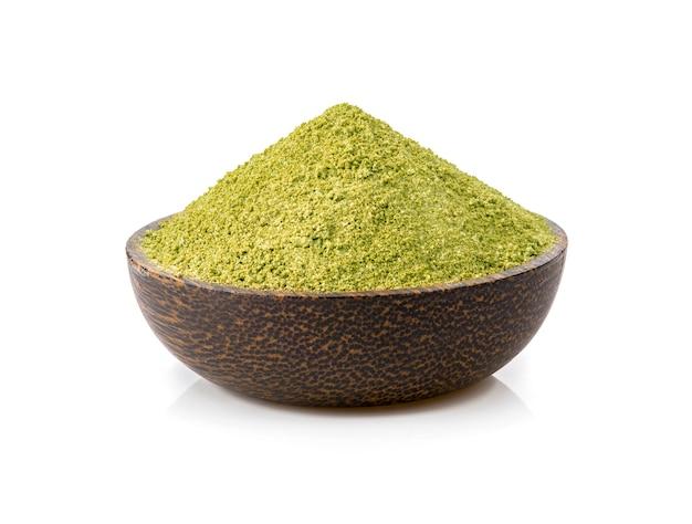Poudre de thé vert dans un bol sur fond blanc