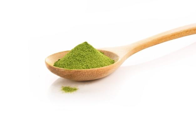 Poudre de thé vert dans une cuillère isolée