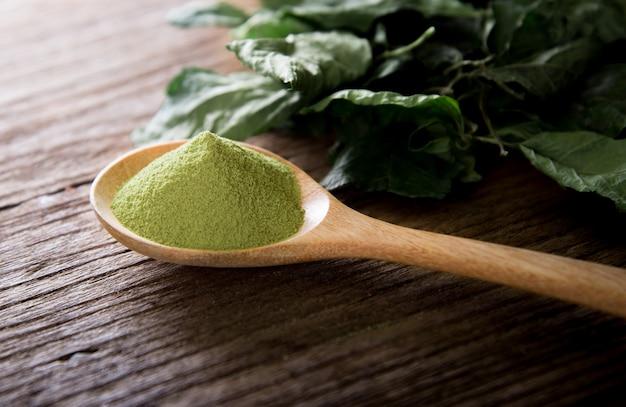 Poudre de thé vert et feuilles de thé vert sur bois.