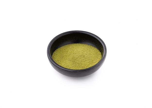 Poudre de thé vert sur fond blanc isolé