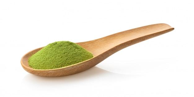 Poudre de thé vert matcha en cuillère de bois blanc