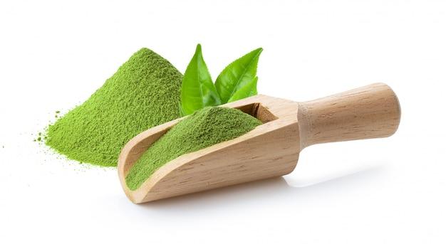 Poudre de thé vert matcha en cuillère en bois et feuille sur blanc