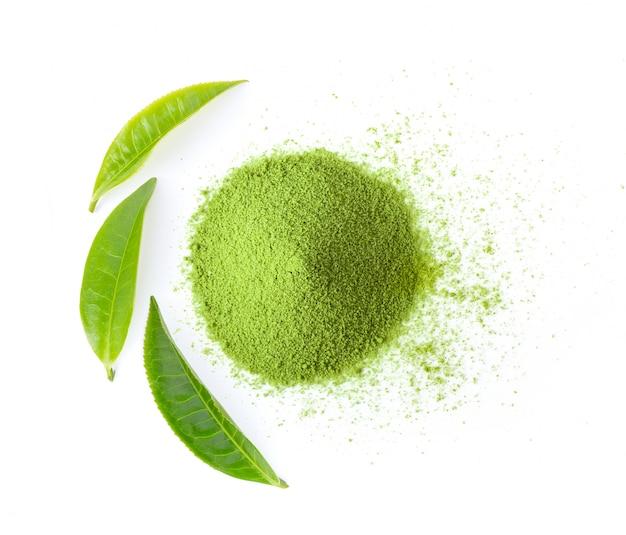 Poudre de thé vert matcha avec des feuilles sur le mur blanc.