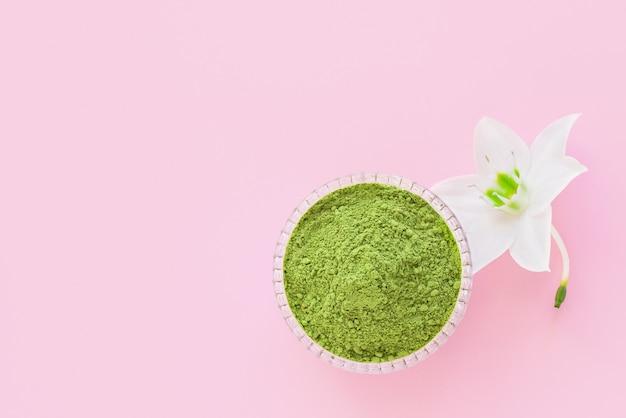 Poudre verte sèche matcha sur fond rose pour faire du thé naturel japonais.