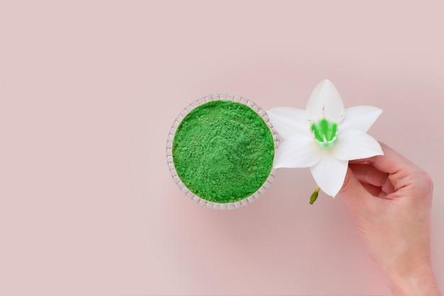 Poudre verte sèche matcha sur une surface rose pour faire du thé naturel japonais.