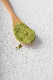 Poudre verte de thé matcha chinois sur un espace de lumière blanche. position verticale