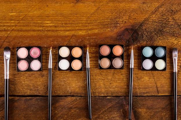 Poudres colorées ombre à paupières avec des brosses sur fond en bois