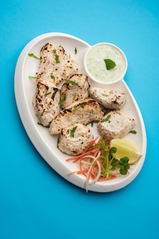 Le poulet afghan indien malai tikka est un kabab crémeux de murgh grillé servi avec une salade fraîche