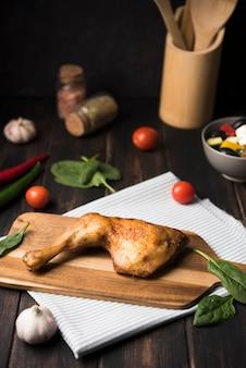 Poulet à angle élevé sur planche de bois avec des ingrédients