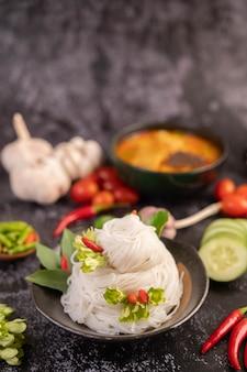 Poulet au curry dans une tasse noire avec des nouilles de riz.