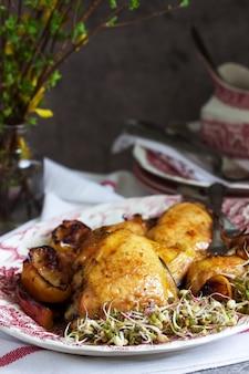 Poulet au four aux pommes, servi avec graines germées et sauce.