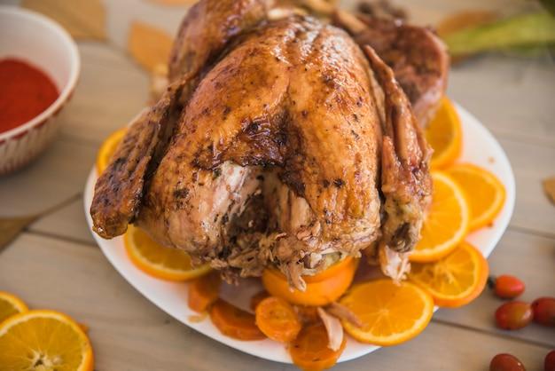 Poulet au four avec des oranges sur une table lumineuse