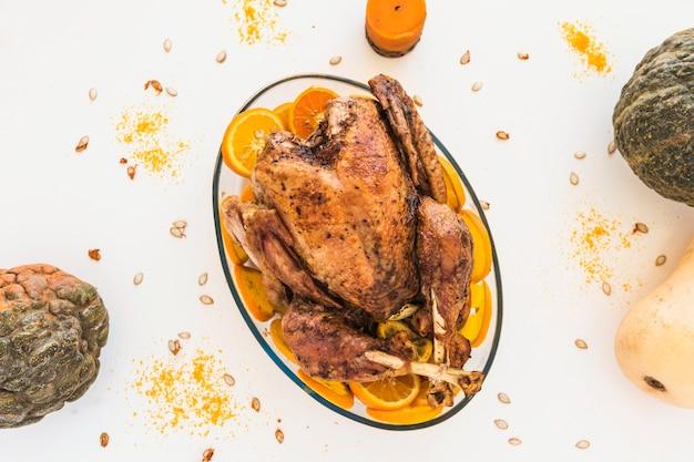 Poulet au four avec des oranges sur la table