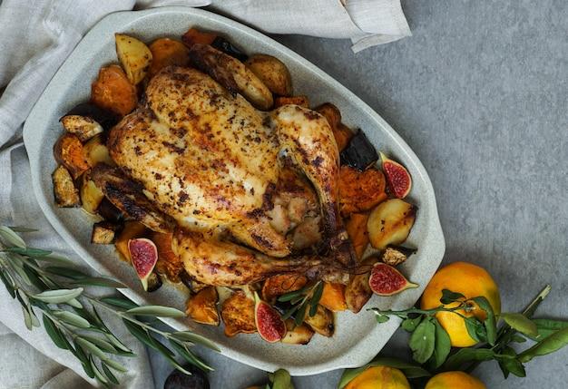 Poulet au four à la peau dorée et croustillante aux raisins et aux pommes de terre, mandarine.
