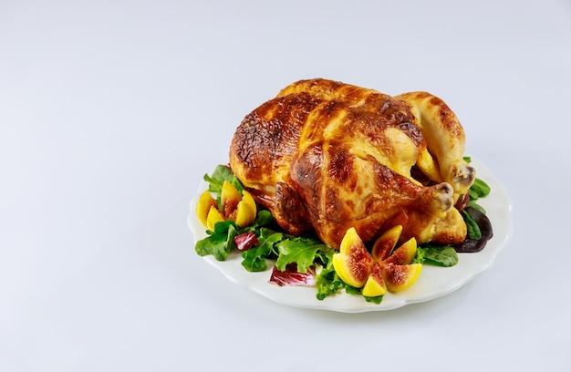 Poulet au four sur plaque blanche avec salade et figues sur mur blanc isolé.