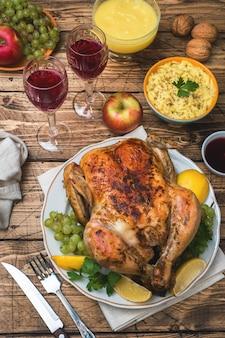 Poulet au four, purée de pommes de terre et verres à vin pour le dîner sur la table de fête.