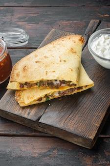Poulet au four et quesadillas au fromage, sur la vieille table de table en bois sombre