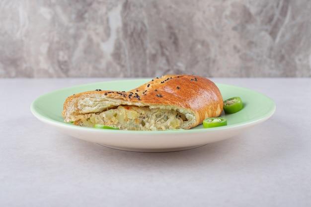 Poulet au pain à côté de piment tranché sur plaque sur table en marbre.