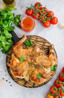 Poulet au tabac, un plat traditionnel de la cuisine géorgienne au poulet frit à l'ail et au poivre. orientation verticale. vue de dessus. fermer.