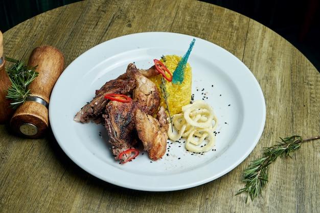 Poulet au tapaka rôti aux épices et un plat de riz sur une plaque blanche. cuisine géorgienne. bouchent la vue sur la nourriture savoureuse.