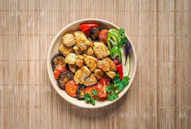 Poulet aux légumes et shiitake sur une serviette en bambou. cuisine chinoise