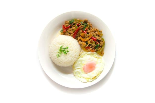 Poulet et basilic sautés dans une cuisine thaïlandaise servis avec riz et oeuf au plat sur une plaque blanche