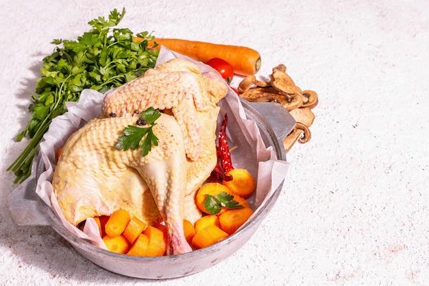 Poulet bio cru entier dans une poêle rustique avec carottes, champignons secs, feuilles de persil frais et ail. oiseau de ferme en plein air prêt à cuisiner. fond de mastic blanc, place pour le texte