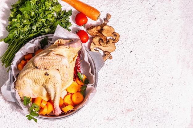 Poulet bio cru entier dans une poêle rustique avec carottes, champignons secs, feuilles de persil frais et ail. oiseau de ferme en plein air prêt à cuisiner. fond de mastic blanc, vue de dessus