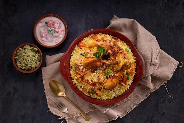 Poulet biriyani à l'aide de riz jeera disposé dans une faïence avec raitha sur fond gris