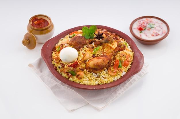 Poulet biriyani à l'aide de riz jeeraarrangé en terre cuite avec raitha sur fond blanc