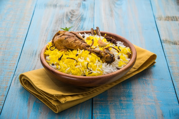 Poulet biryani authentique servi dans un bol ou une assiette sur fond coloré ou en bois. c'est une délicieuse recette de riz basmati mélangé avec du poulet mariné épicé servi avec une salade. mise au point sélective