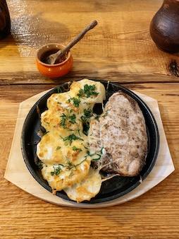 Poulet chaud au four avec pommes de terre et fromage dans un style rustique