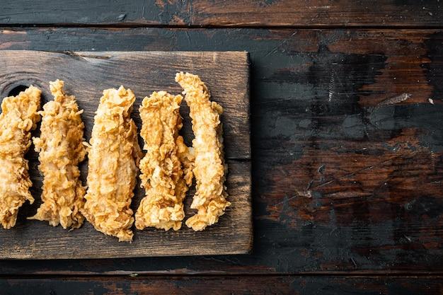 Le poulet croustillant colle de la viande sur un fond en bois foncé, à plat, avec un espace pour le texte.