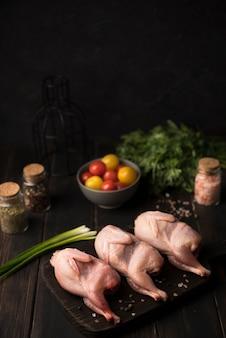 Poulet cru à angle élevé sur planche de bois avec des ingrédients