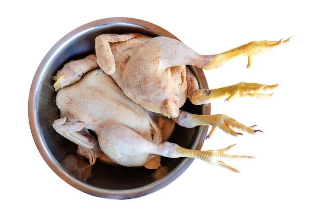 Poulet cru dans un bol en métal pour nettoyer et préparer la nourriture, la viande