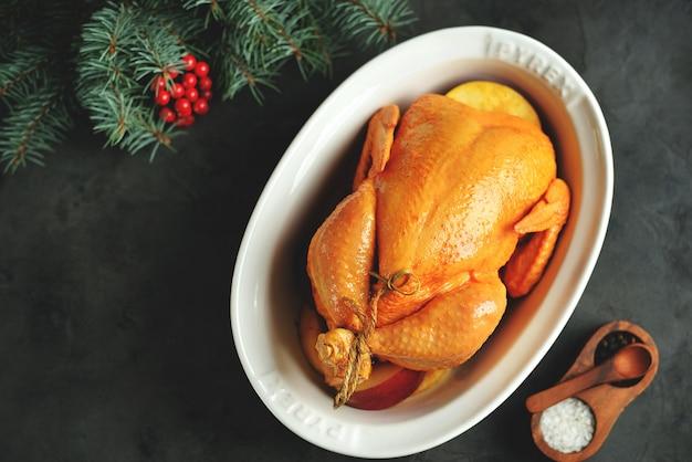 Poulet cru entier mariné à l'huile d'olive, sauce soja, vinaigre de vin blanc avec curcuma, thym et tranches de pomme. vue de dessus.