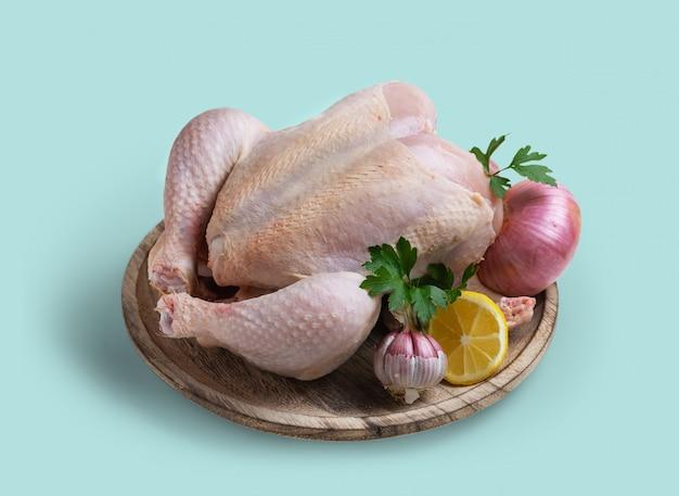 Poulet cru avec des ingrédients pour faire du bouillon, sur isolé