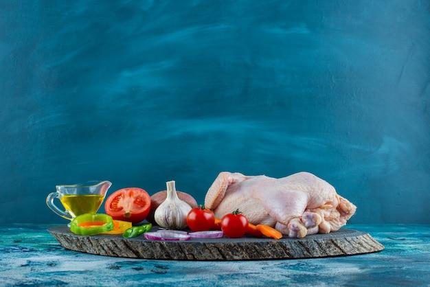 Poulet cru, légumes et huile sur une planche sur la surface bleue