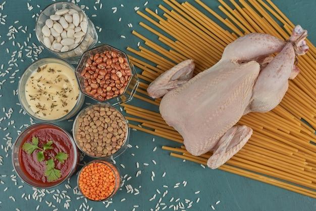 Poulet cru avec pâtes, haricots et sauces.