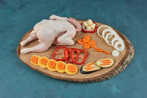 Poulet cru sur une planche de bois avec des herbes et des légumes.